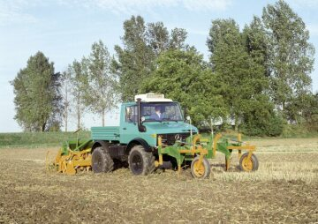 Unimog U1400, model series 427 with front-mounted cultivator and seed drill cultivating soil