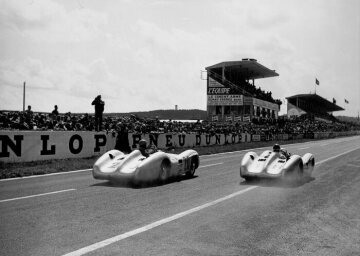 The eventual race winner Juan Manuel Fangio (start number 18) and second-placed Karl Kling (start number 20), both in the Mercedes-Benz W 196 racing car.
