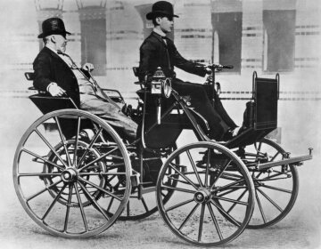 "Gottlieb Daimler enjoying a ride in the back seat of his ""Motor Carriage"", driven by his son Adolf."